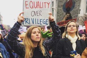Femme tenant une pancarte Equality over privilege lors de la Women's March